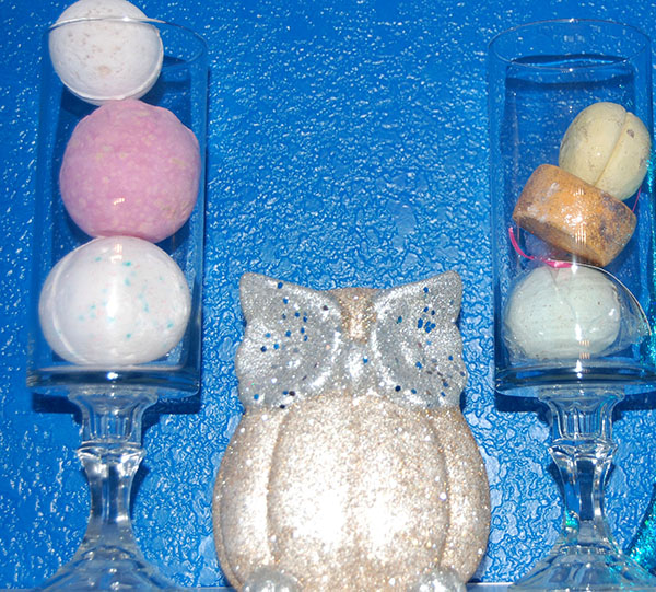 apothecary jars with lush bath bombs and gold and silver owl