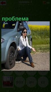 женщина на дороге не может заменить колесо, проблему по телефону решает
