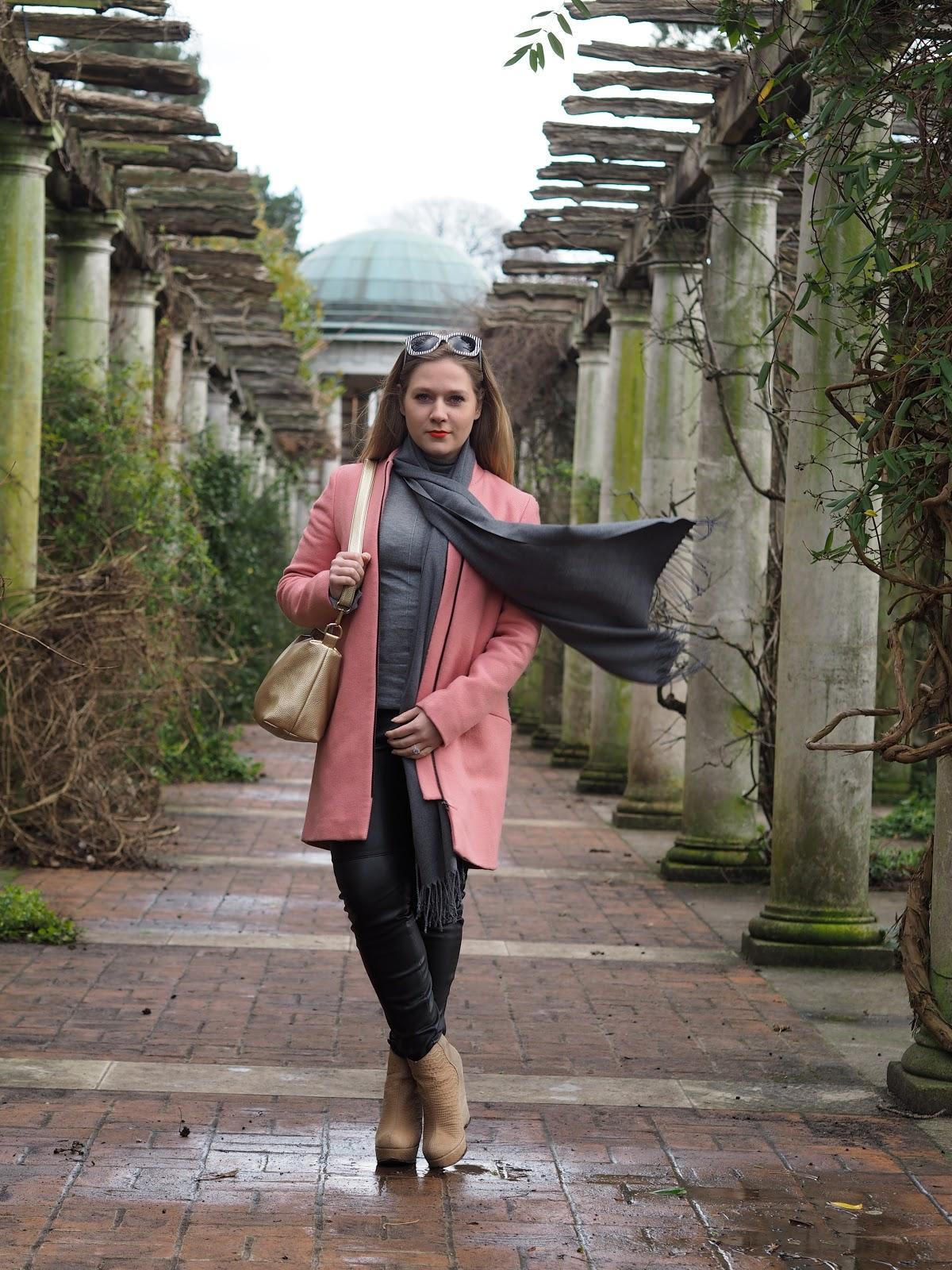 Blonde girl wearing winter clothes standing between pillars wearing pink coat