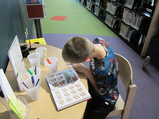 a person looks at a book of illustrations from Captain Underpants and works on making an illustration himself to put on a button