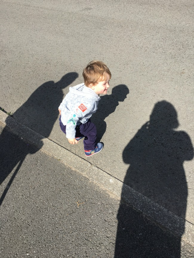 Our-weekly-journal-15th-may-2017-Cardiff-Bay-and-shadows-toddler-crouching-by-three-shados-his-own-and-two-adults