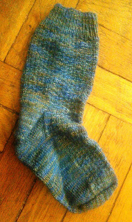 A finished sock laying flat, the foot is folded up.  The sock is textured, made in blue with flecks of brown and gold.