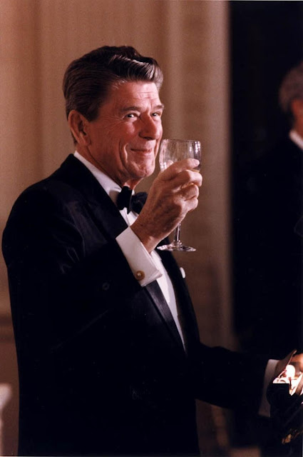 President Ronald Reagan looking handsome in a tux, with a glass of champagne.