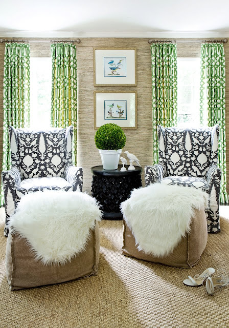Living room with two sea grass ikat armchairs, woven sea grass sisal rug, green graphic curtains and two large ottomans covered with a furry throw