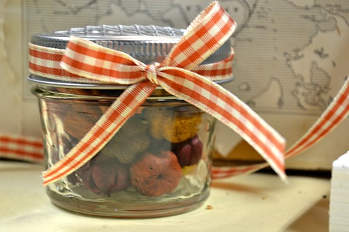 Small mason jar with orange bow and tiny pumpkins