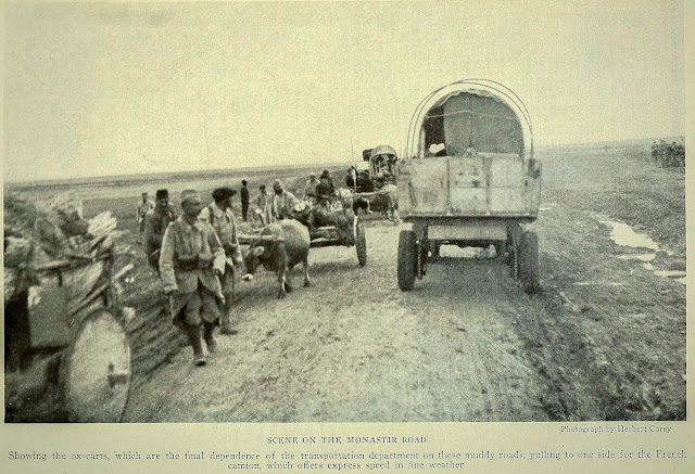 SCENE ON THE MONASTIR ROAD Photograph by Herbert Corey Showing the ox-carts, which are the final dependence of the transportation department on these muddy roads, pulling to one side for the French camion, which offers express speed in line weather