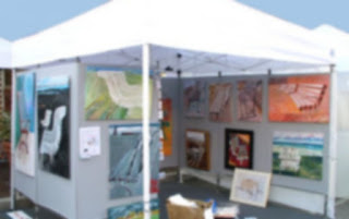 Booth filled with art at outdoor arts and crafts fair.