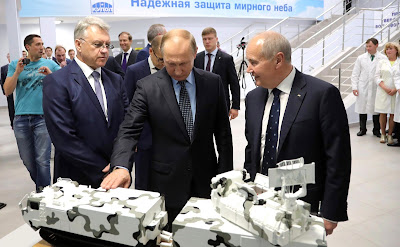 Vladimir Putin with a model of a ZRK-TOR-M2DT military vehicle