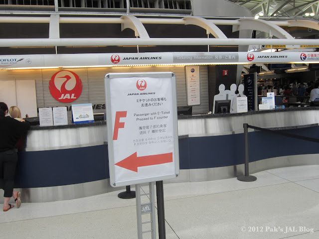 Sign telling JAL passengers with e-ticket to proceed to counters located in Aisle F at New York JFK