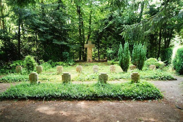 Auf einem kleinen Friedhof im Wald stehen Grabsteine. Hinten steht ein großes Kreuz
