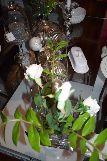 Dining table center pieces with zz plant foliage; white roses; silver balls
