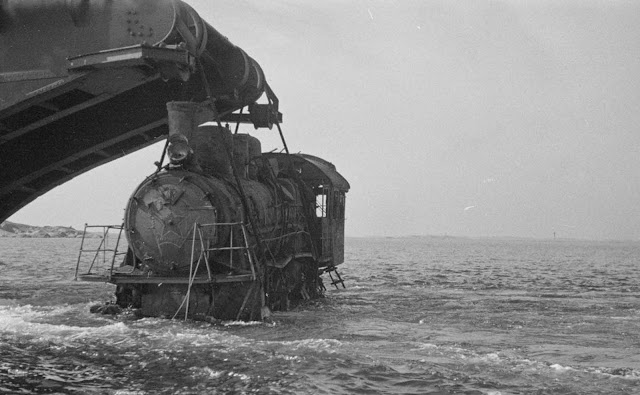 A barge lifts a wrecked locomotive.