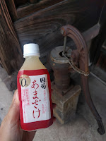 350mlのペットボトルの甘酒と後ろに井戸の錆びたポンプ