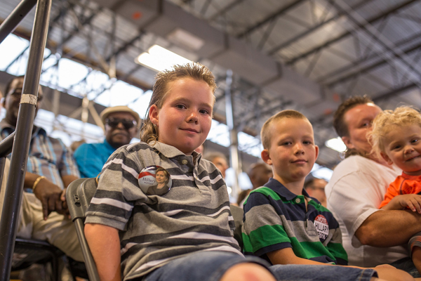 image of two little white boys sitting in the crowd at a Hillary rally, wearing 'Hillary' buttons
