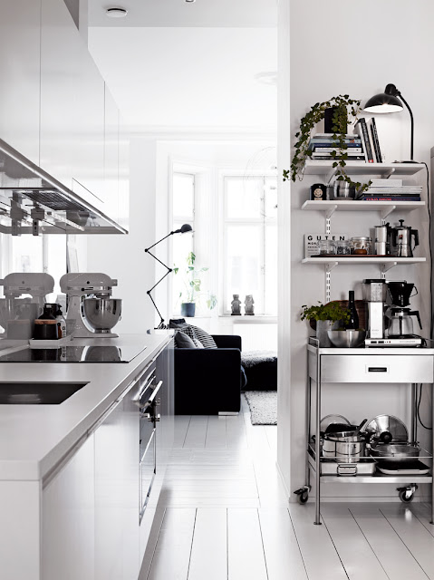 small white kitchen apartment stainless steel cart laminant counters white wood floors