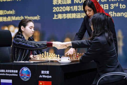Certaines photos lors du lancement des parties du championnat du monde montrent qu'elle porte parfois un voile, mais pas systématiquement - Photo © FIDE