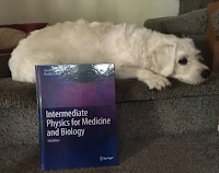 Suki Roth next to the textbook Intermediate Physics for Medicine and Biology.