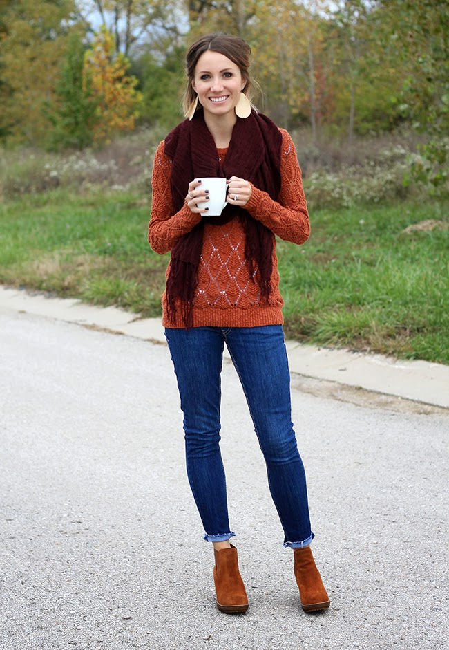 Maroon scarf, orange sweater, ankle boots and cuffed denim