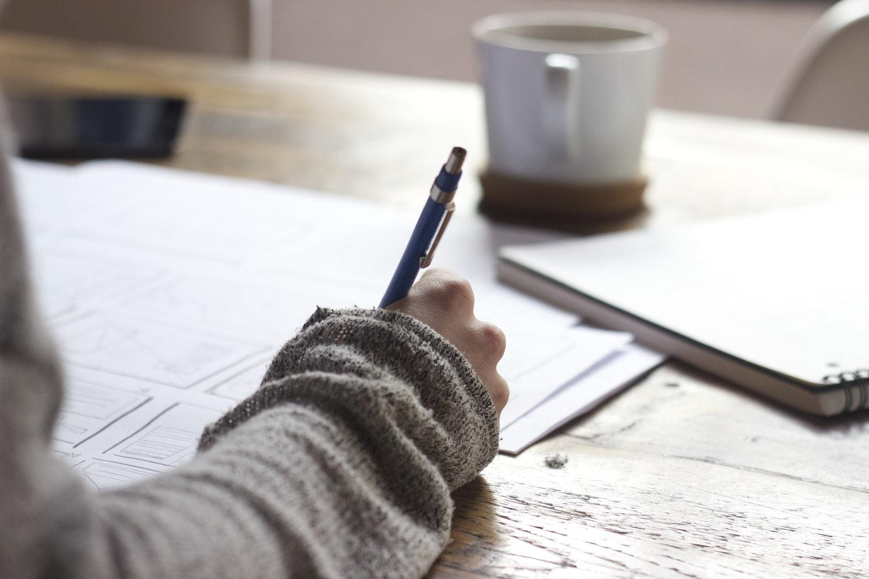 woman at university sat at a table writing