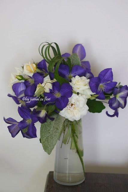 imagine poza buchet clematis mov si trandafiri albi in vaza transparenta