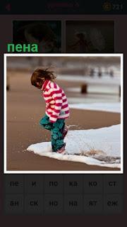 в пене на берегу стоит девочка и играет