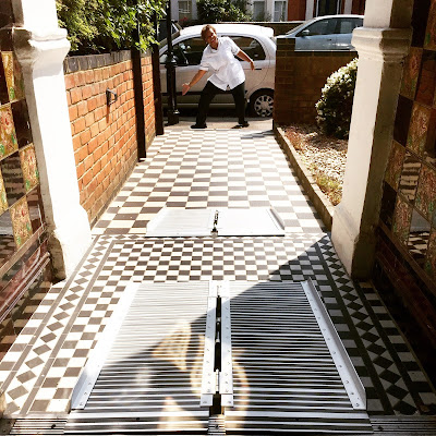 It's a long narrow entrance with graduated steps with level platforms in-between. There are three ramps over the black and white tiles. At the bottom of the steps, so on the pavement, the receptionist doing a happy dance.