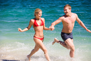 Photo of a Young Couple in Swimsuits Running Hand in Hand on the Beach