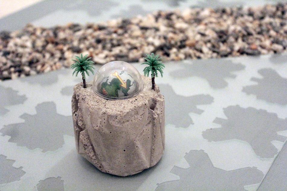 Hito piedra es un objeto pequeño de cemento con una brujula y unas palmeras de plástico