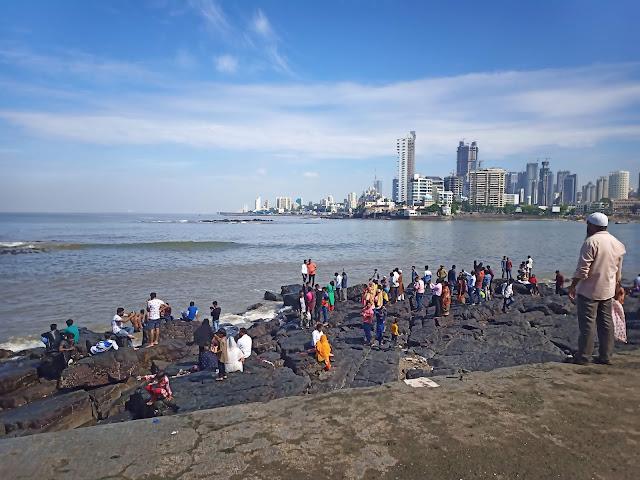 View of rocks and sea behind Haji Ali Dargah, Mumbai skyline to the right