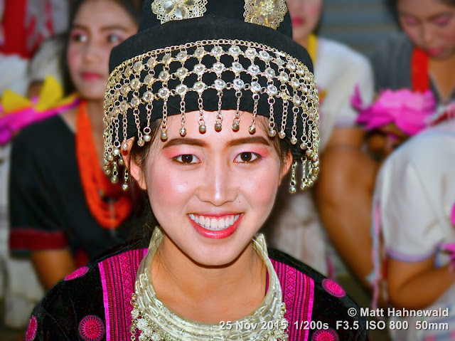 Matt Hahnewald; Facing the World; people; portrait; headshot; nightshot; colour; flash; Nikon DSLR D3100; 50 mm prime lens; Nikon SB-400; Asia; Southeast Asia; Northern Thailand; Chiang Mai Province; Mae Chaem; Yi Peng; Thai hilltribe costume; Thai hilltribe culture; Thai hilltribe headgear; street parade; Thai girl; traditional costume; eye contact; tradition; world cultures; travel; travel destination; festival; makeup; teeth; Miao people; H'mong headgear