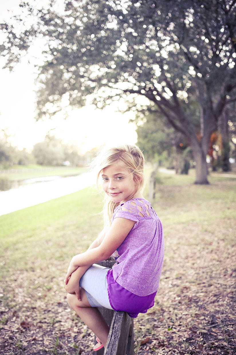 Little girl sitting on a fence