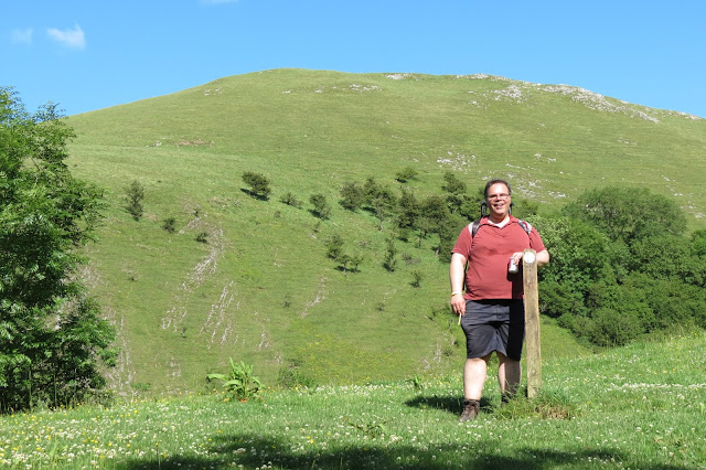 Rich leaning against a wooden marker post. In the background, a steep green hillside with patches of exposed limestone.