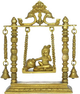 Baby Krishna on a swing decorated with peacocks.
