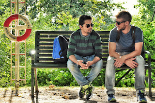 Two men in jeans chatting outdoors on a park bench
