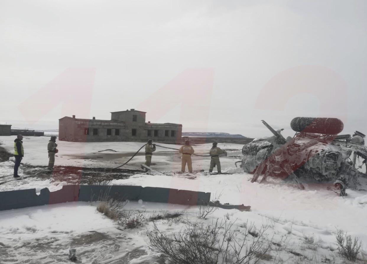 Ugunsdzēsēji tur rokās šļūteni pie apledojuša helikoptera vraka ziemas laikā