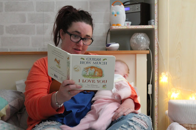 mother reading guess how much i love you to baby at bedtime