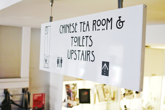 Close up of a sign within the tea rooms that points to the Chinese tea room and toilets