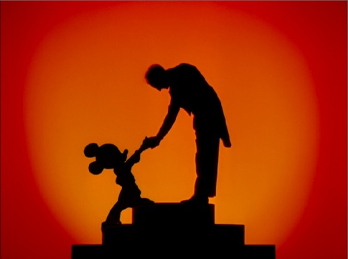 Conductor Leopold Stokowski shaking hands with Mickey Mouse in Fantasia 1940 animatedfilmreviews.filminspector.com