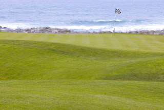 manicured golf greens, golf flag flying on a beach side beach view green
