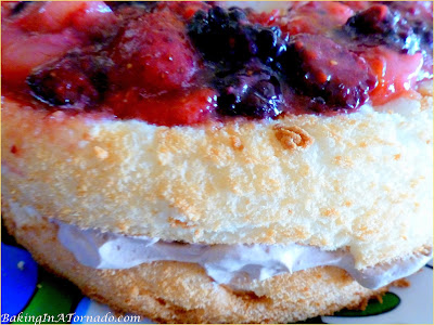 Angel Cake with Chocolate Whipped Cream and Berries, heavenly flavors marry in a light and fluffy cake layered with chocolate whipped cream and mascerated berries. | Recipe developed by www.BakingInATornado.com | #recipe #cake #dessert