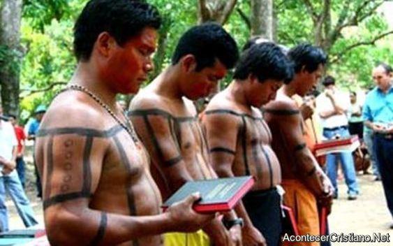 Pobladores de tribu indígena recibiendo Biblias.