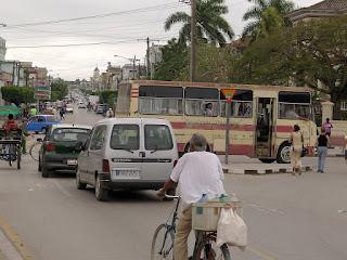 Verkehrsreiche Straße, Autos, Fußgänger, Bus, Fahräder, Bicitaxis.