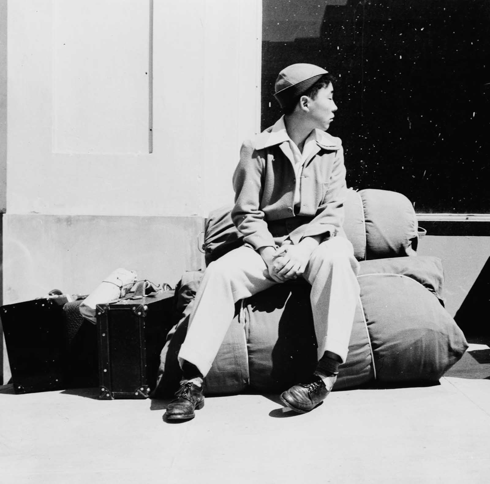 A boy sits on his belongings as he awaits relocation from San Francisco.