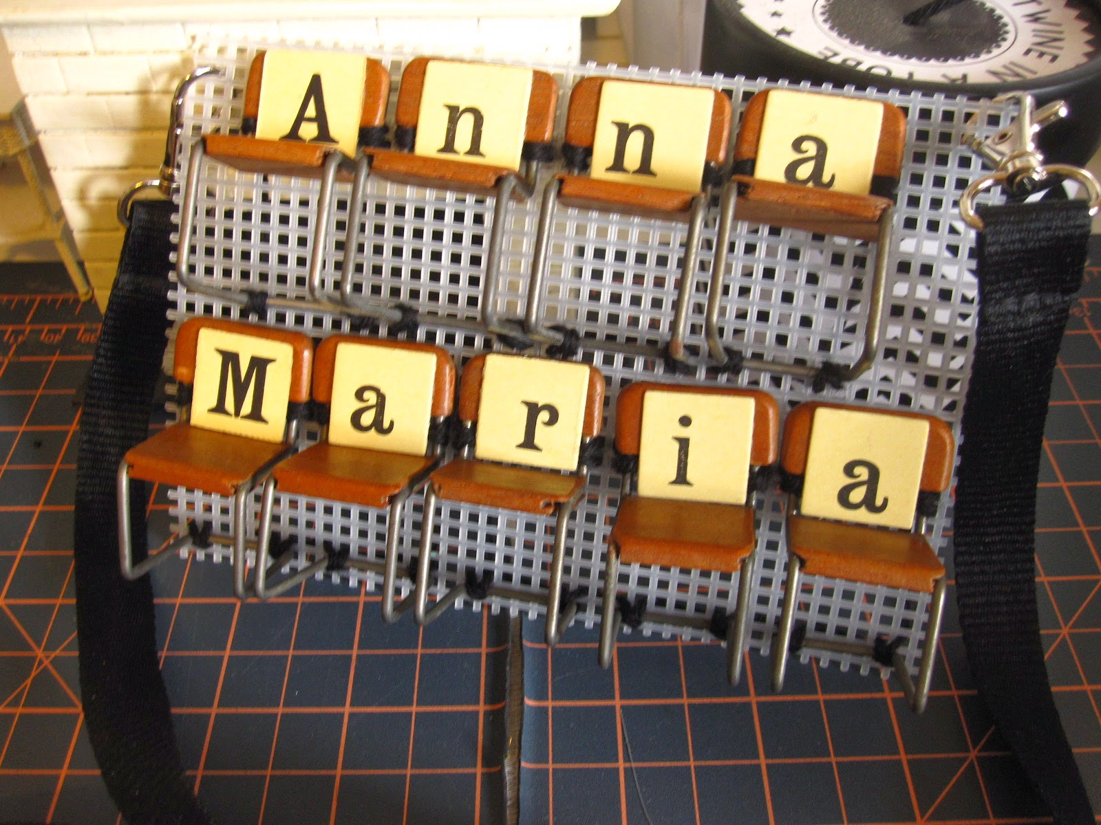 Name tag made from vintage miniature chairs sewn onto plastic canvas with vintage game letters attached to the seats,