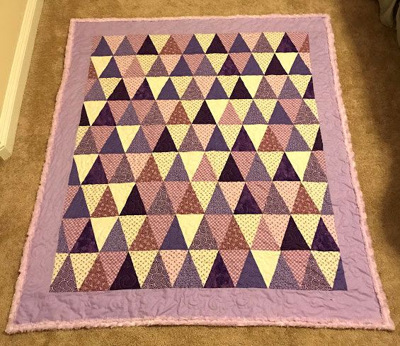 Triangle quilt in purple and white.