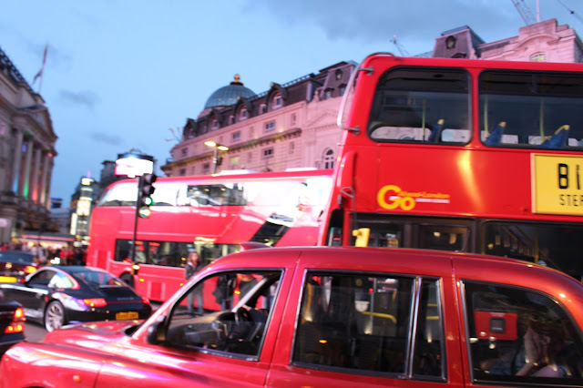 Piccadilly Circus at dusk with taxis, big red buses and cars