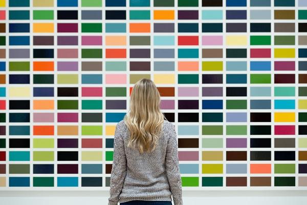 imagem de moça olhando para uma tela com retângulos coloridos, dispostos aleatoriamente