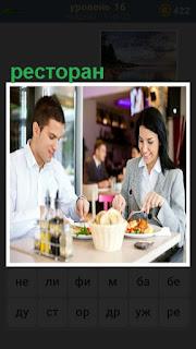 за столом в ресторане мужчина с женщиной принимают пищу