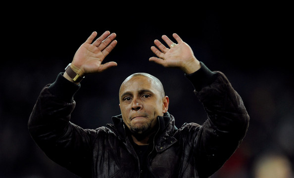 Former Real Madrid player Roberto Carlos waves to supporters after he was presented with a trophy for his achievements at the club by president Florentino Perez during the La Liga match between Real Madrid and Levante at Estadio Santiago Bernabeu on February 12, 2012 in Madrid, Spain