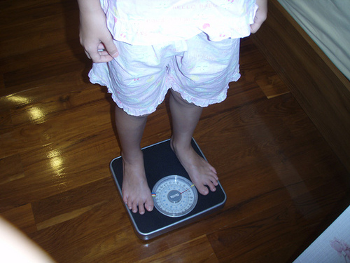 Woman Standing on the Bathroom Scale Weighing Herself